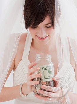 Bride holding jar of money, studio shot